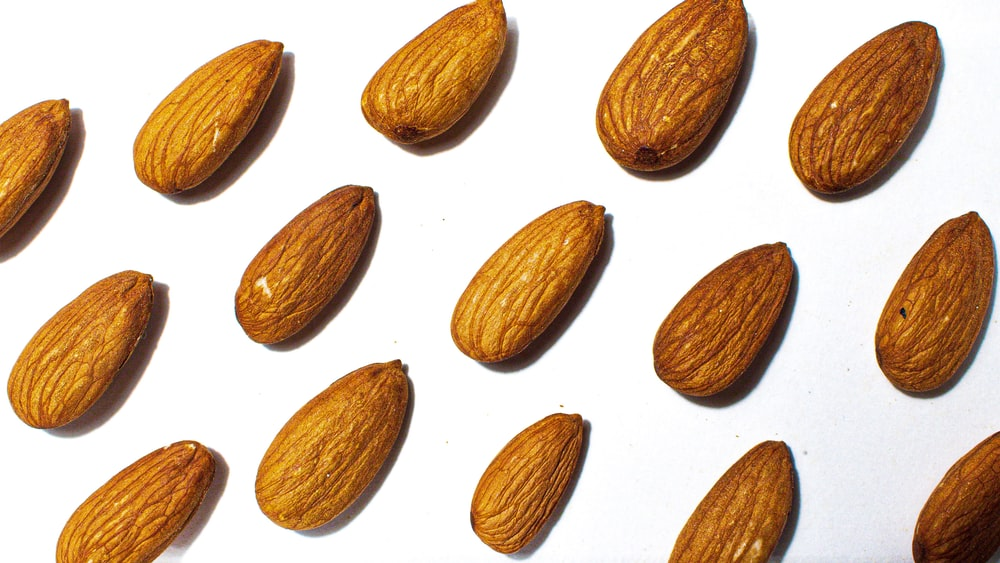 brown almond nuts on white background