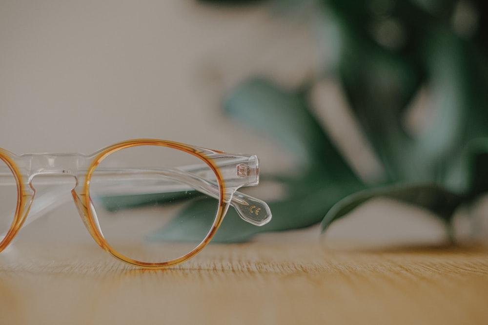 yellow framed eyeglasses on white textile