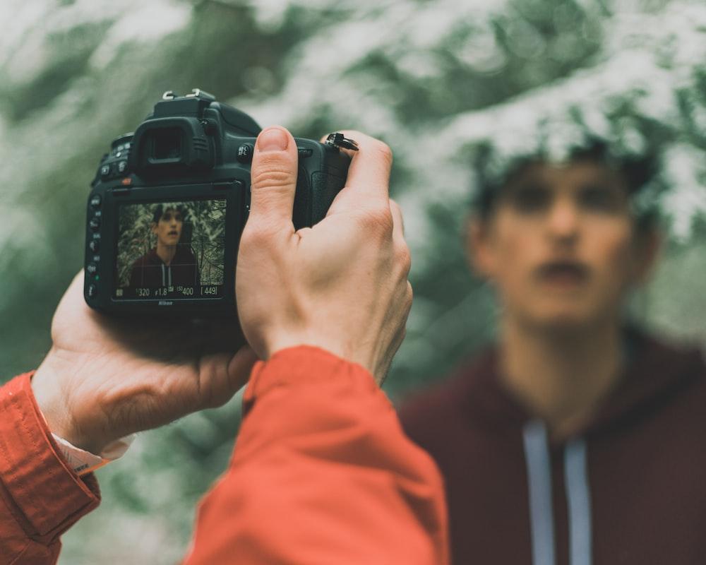 man in orange jacket holding black dslr camera