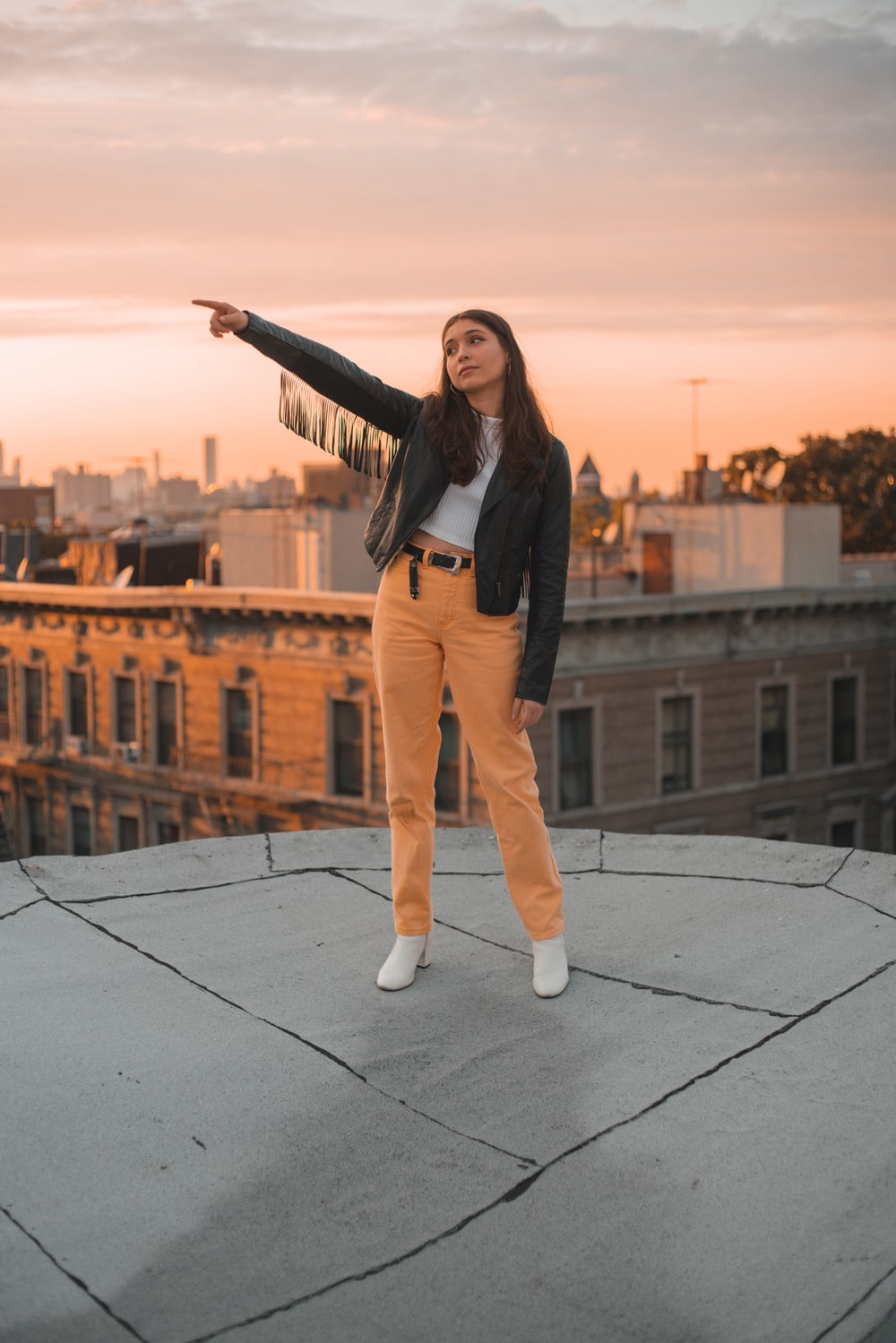 woman in black long sleeve shirt and brown pants standing on black tile floor during daytime