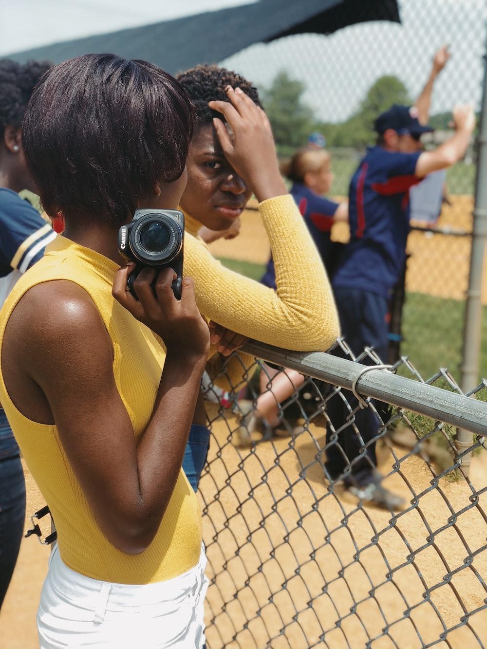 woman in yellow tank top holding black dslr camera