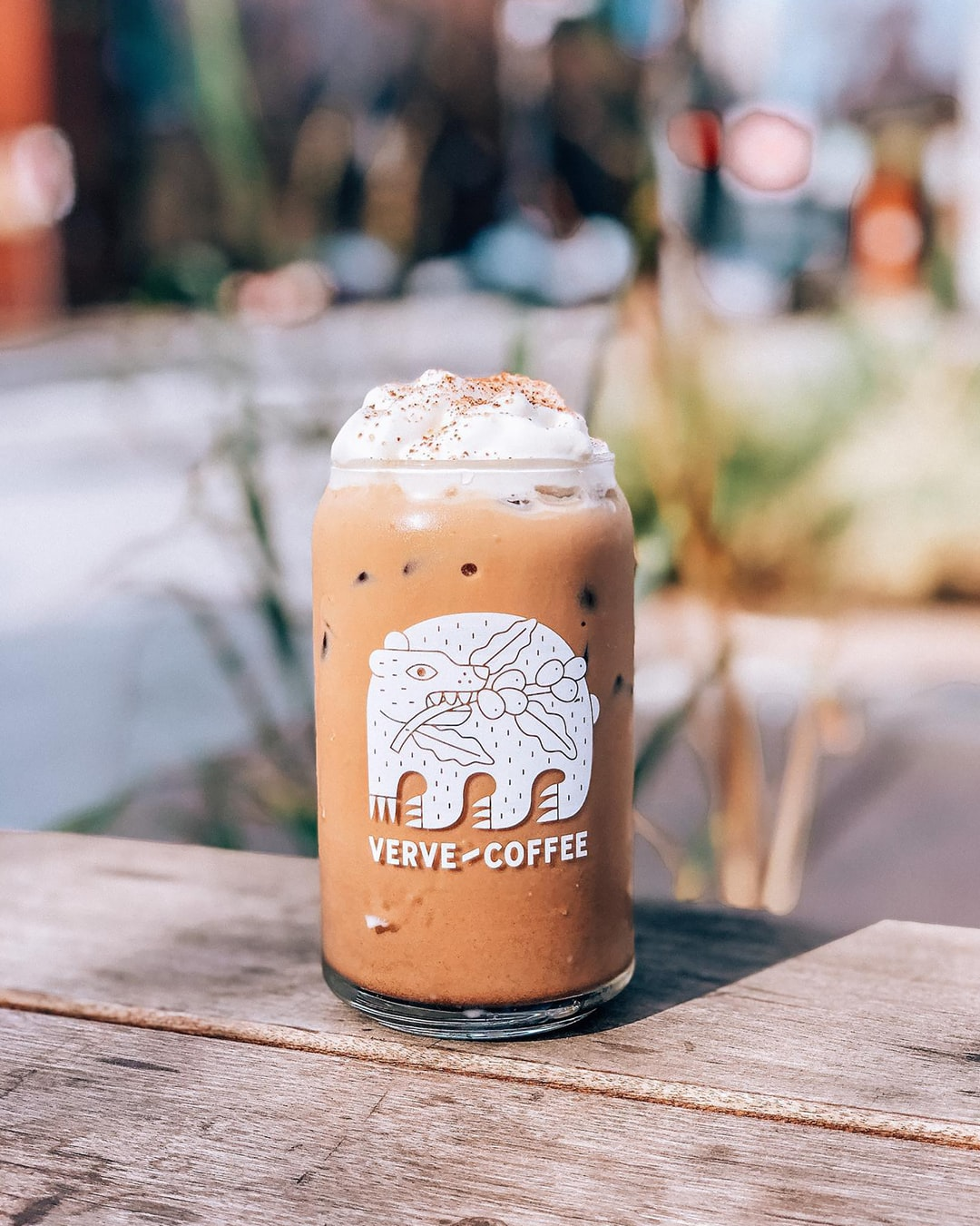 An iced mocha topped with whipped cream and sprinkled with chocolate powder in a glass cup on an outdoor wooden table.