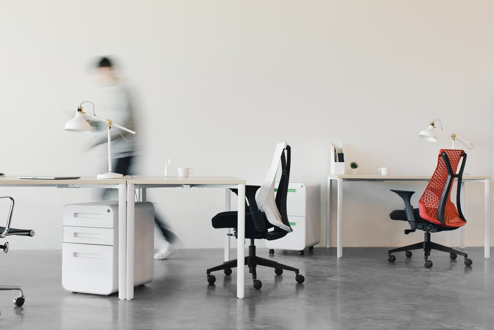 woman in white long sleeve shirt sitting on black office rolling chair