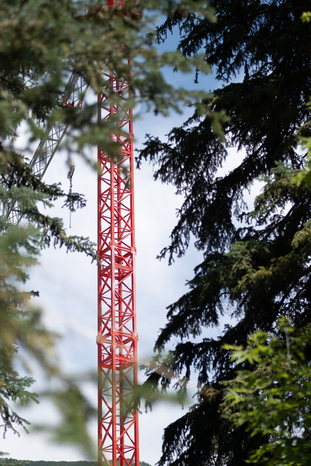 red tower near green trees during daytime