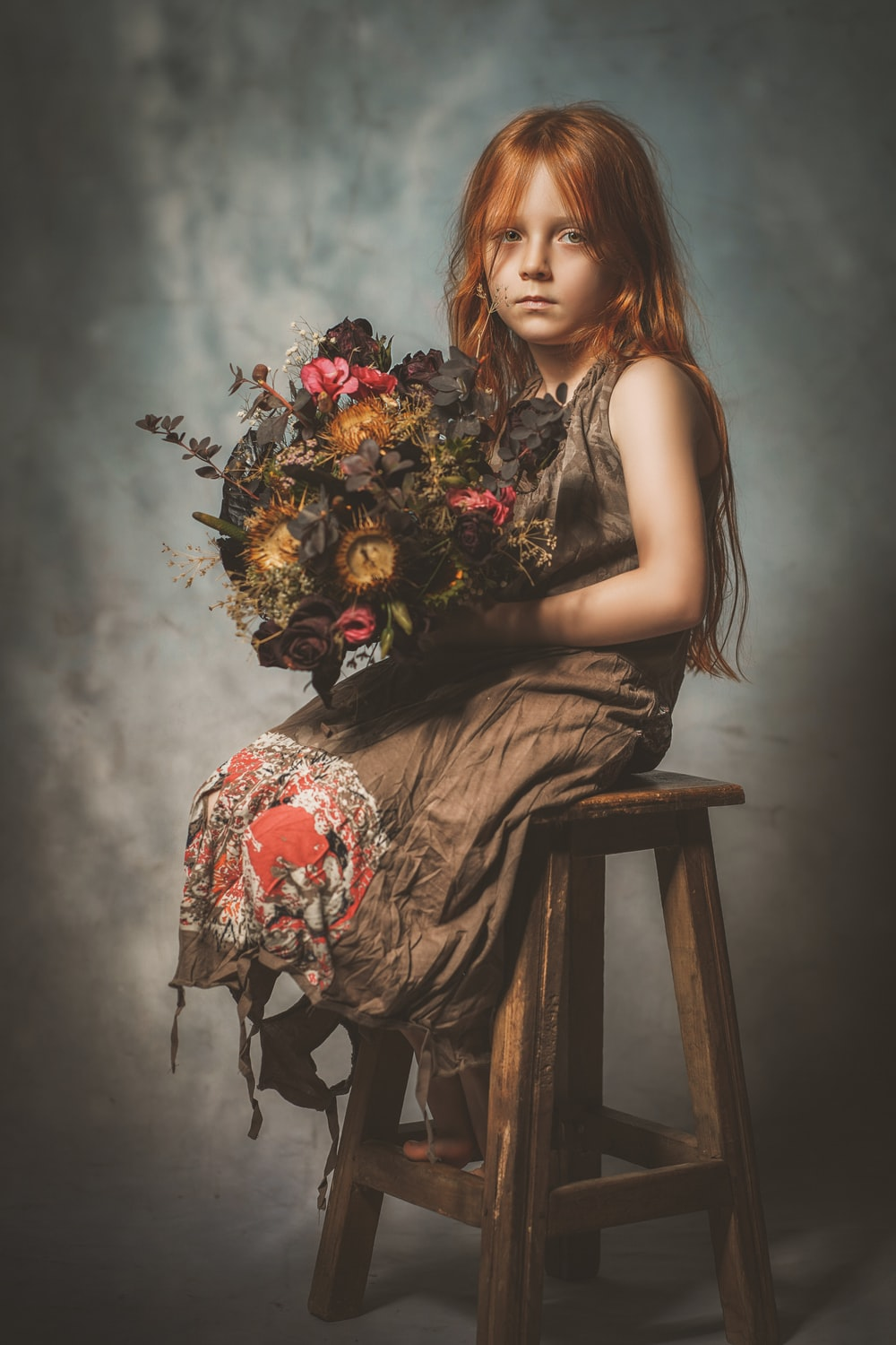 woman in black and red floral sleeveless dress holding bouquet of flowers