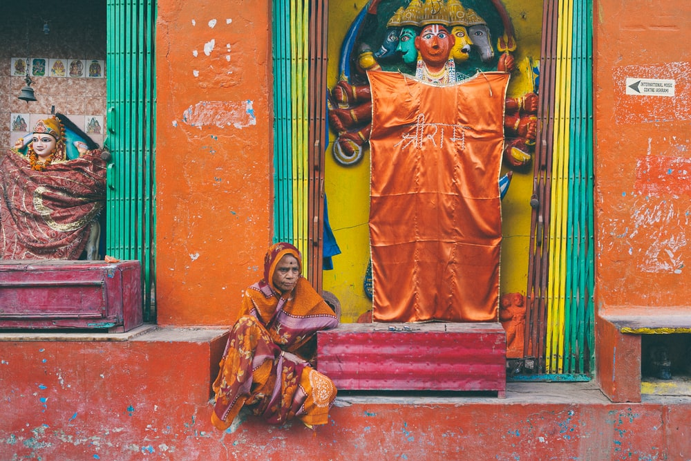 man in orange and yellow traditional dress standing beside red concrete wall