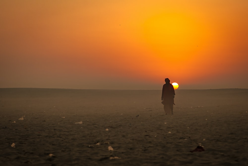 man in yellow hoodie standing on beach during sunset