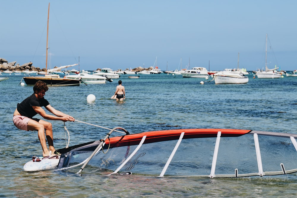 people riding on red and white boat on sea during daytime
