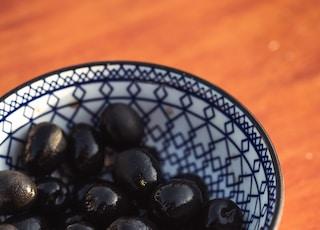 black round fruits on white and blue ceramic bowl