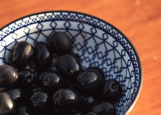 black round fruits on white and blue ceramic bowl