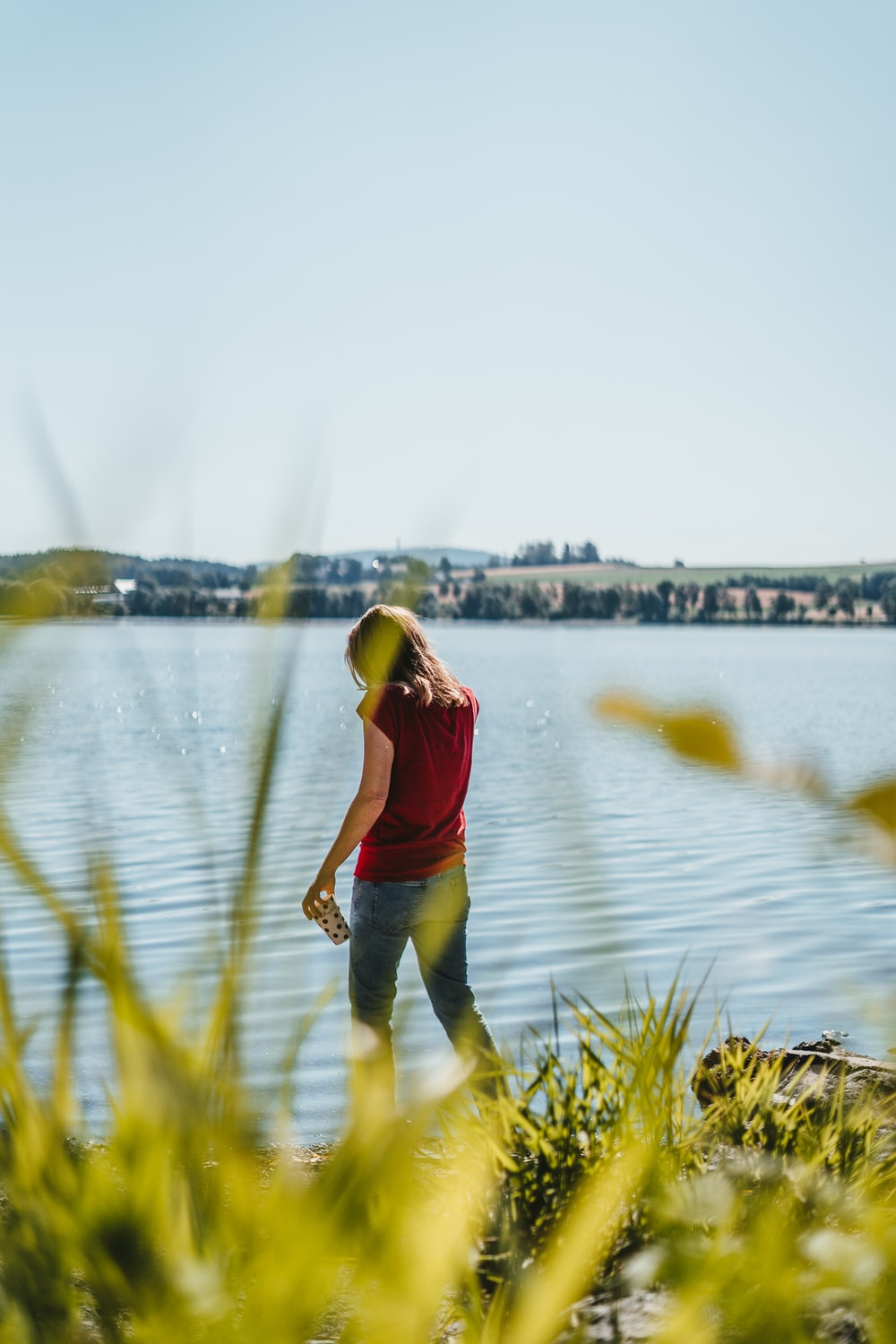 woman in red tank top and black pants standing on green grass near body of water