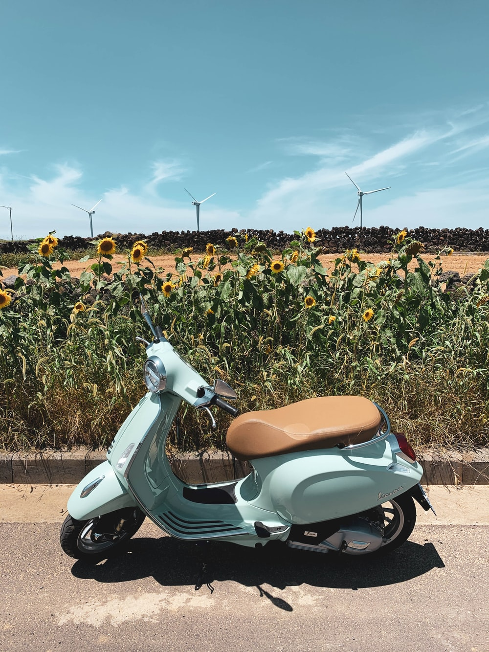 white and brown motor scooter on green grass field during daytime