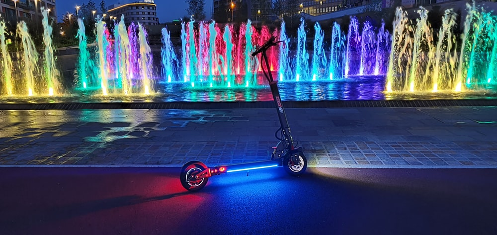 red and black kick scooter near water fountain