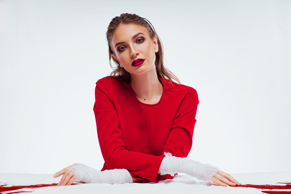 woman in red long sleeve shirt sitting on white textile