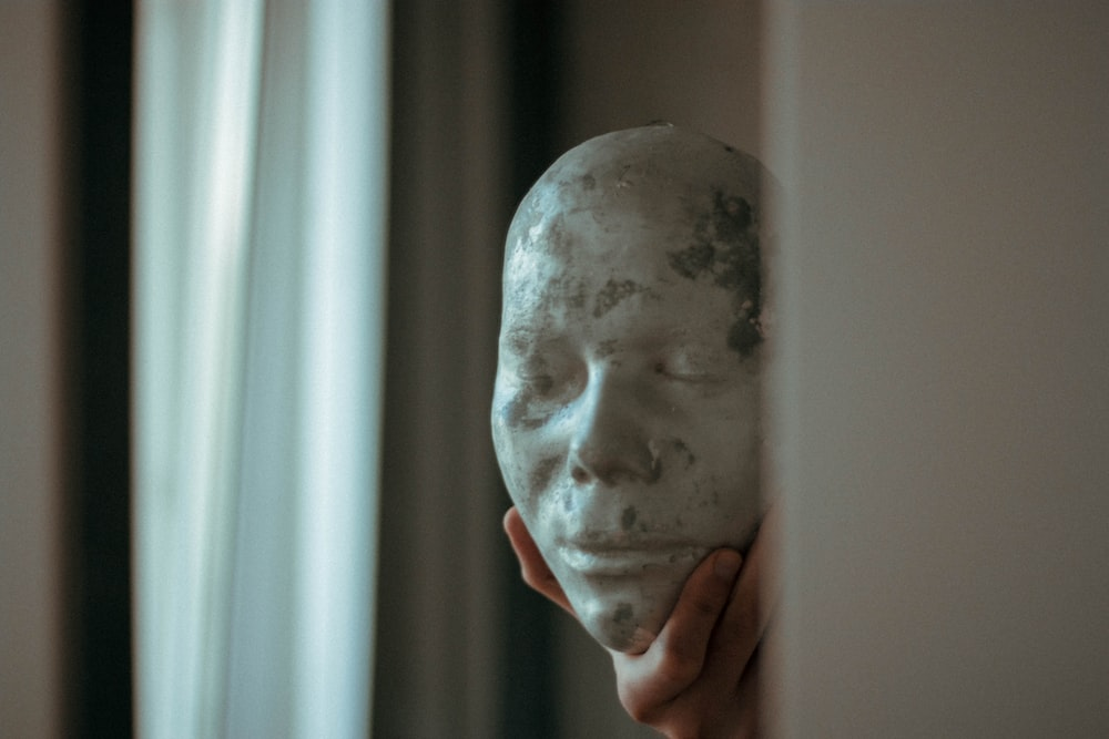 person holding white face mask