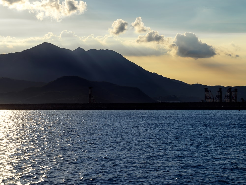 silhouette of mountain near body of water during daytime