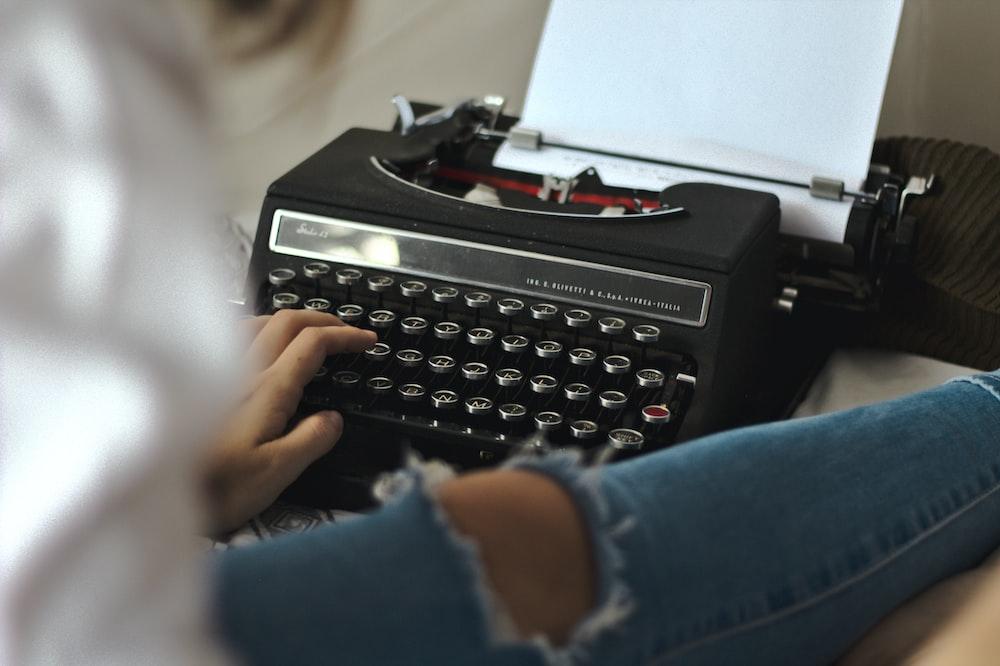 person in blue long sleeve shirt holding black typewriter