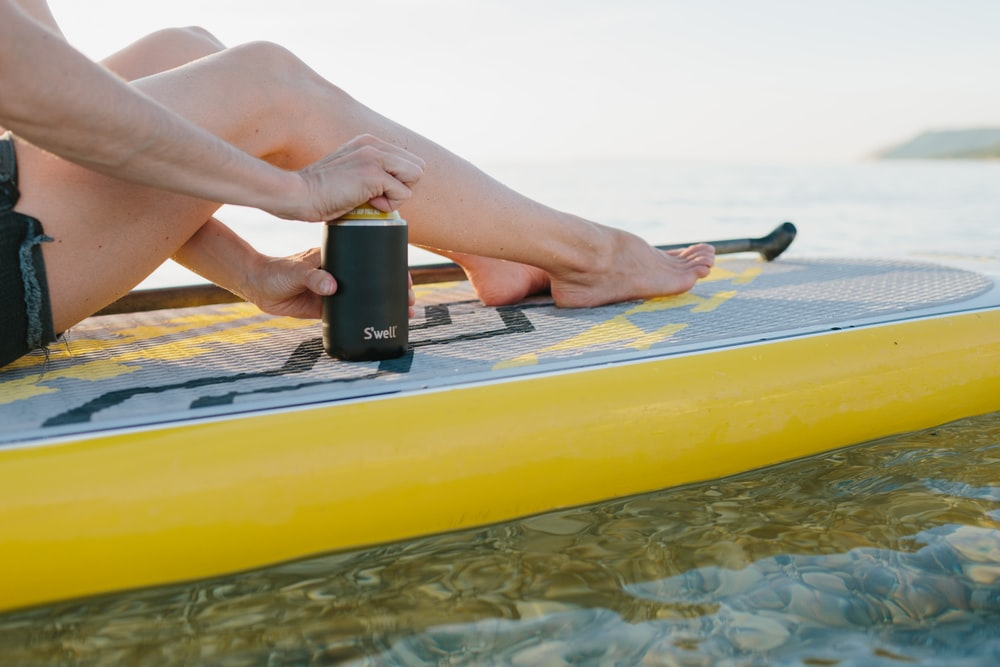person holding black smartphone on yellow inflatable bed