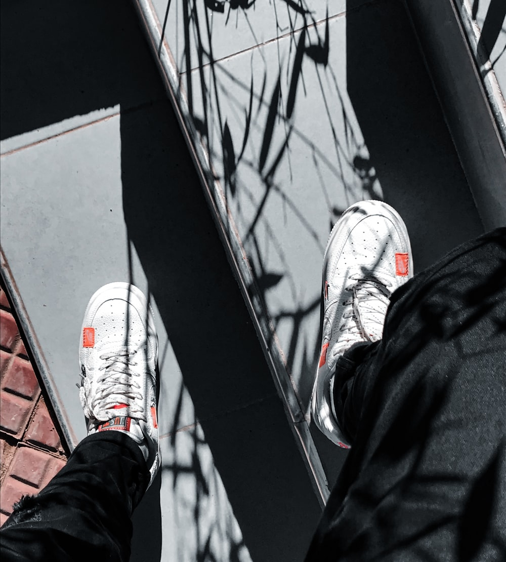 person in black pants and white and red sneakers standing on black and white skateboard during