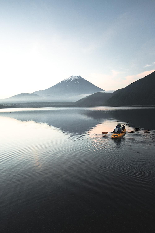 yellow kayak on calm water near mountain during daytime