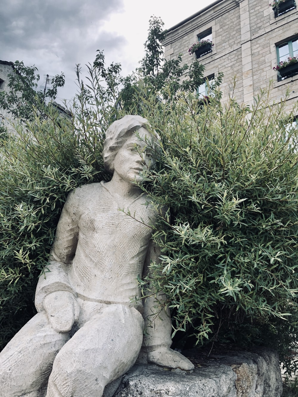 woman statue near green plants during daytime