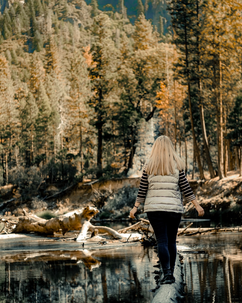 woman in black and white striped long sleeve shirt and black pants standing on river during