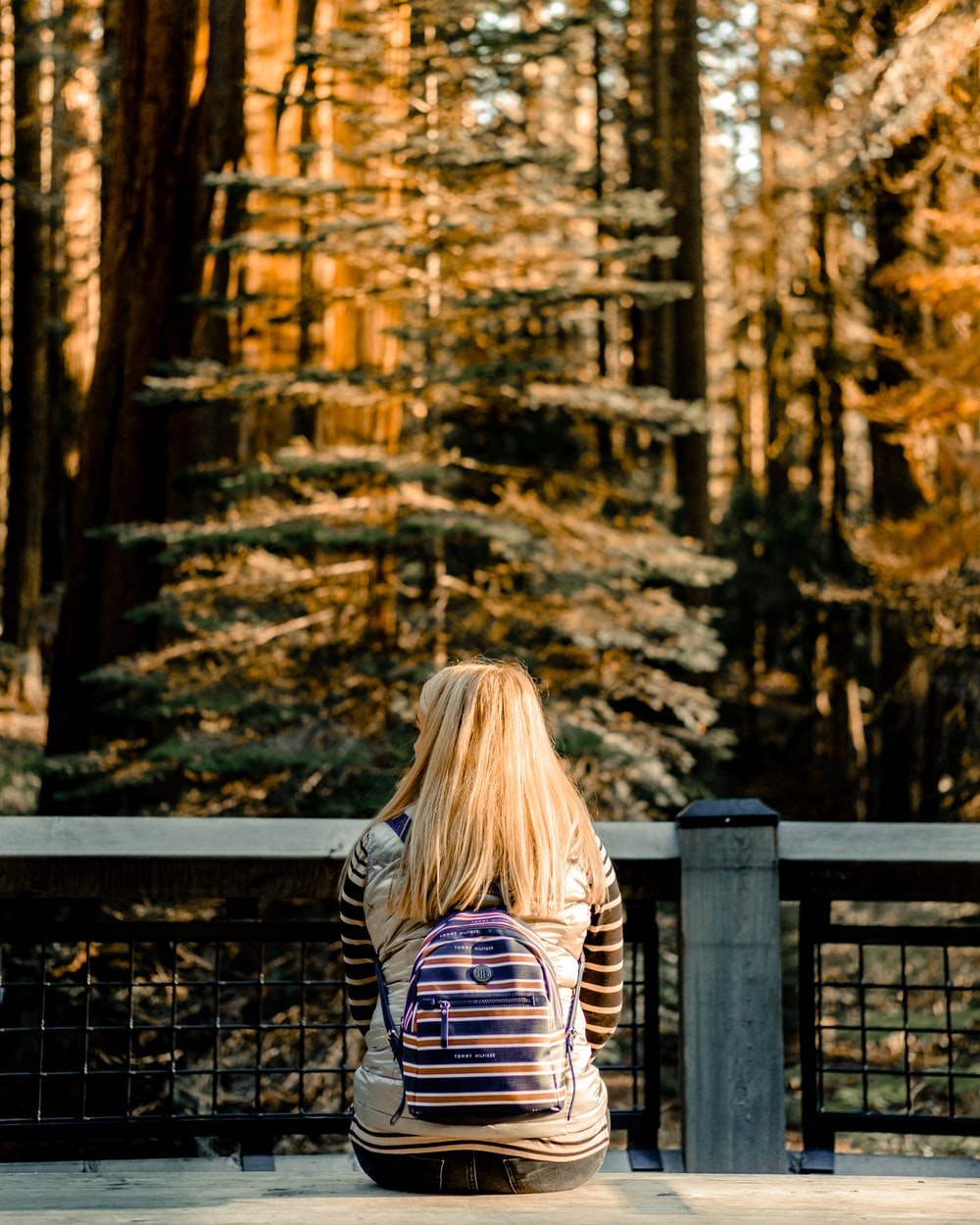woman in black and white striped long sleeve shirt standing near brown wooden fence during daytime