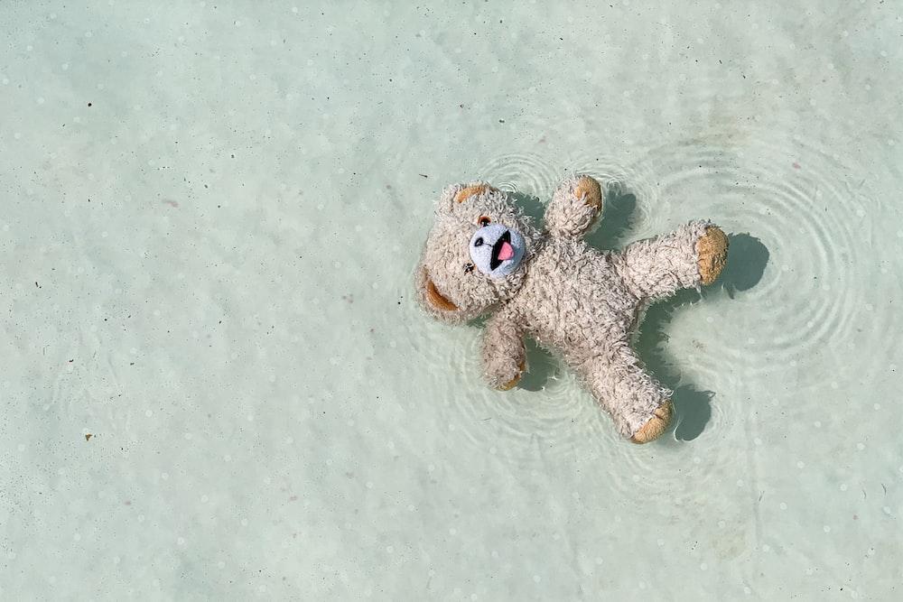 brown and white dog plush toy on white textile