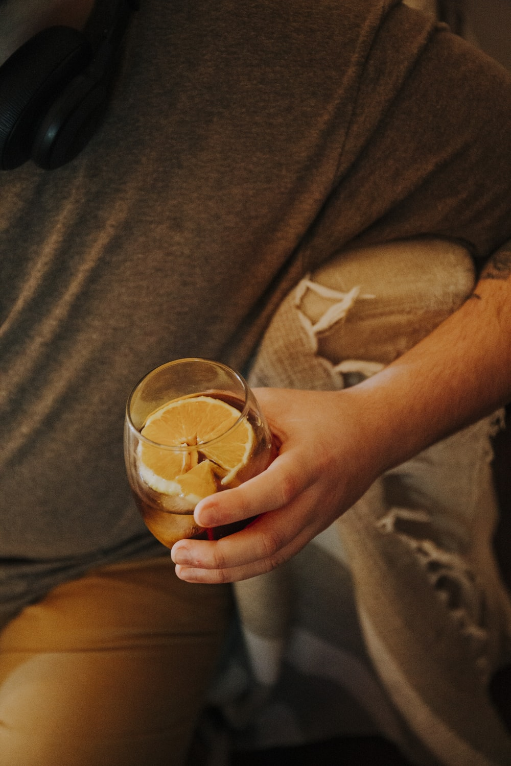 person holding clear drinking glass with brown liquid
