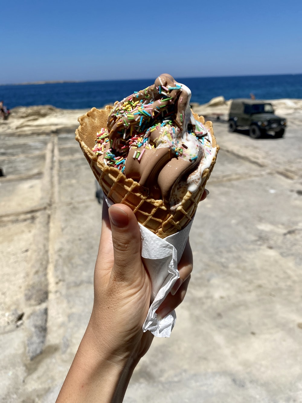 person holding ice cream cone with chocolate and strawberry ice cream