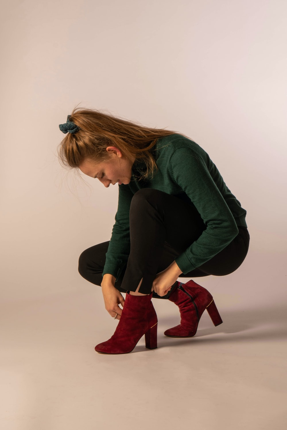 woman in green long sleeve shirt and red boots sitting on white floor