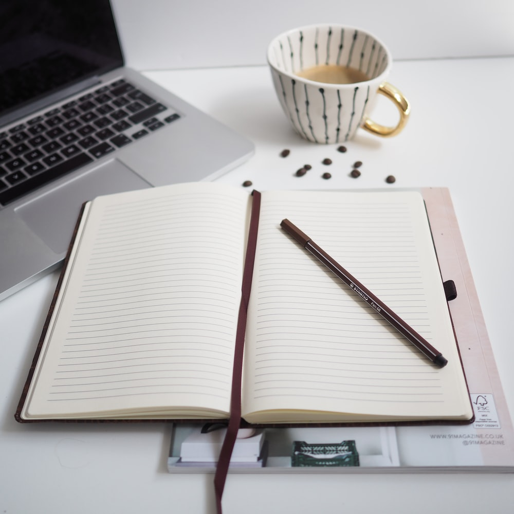 white notebook beside silver macbook pro