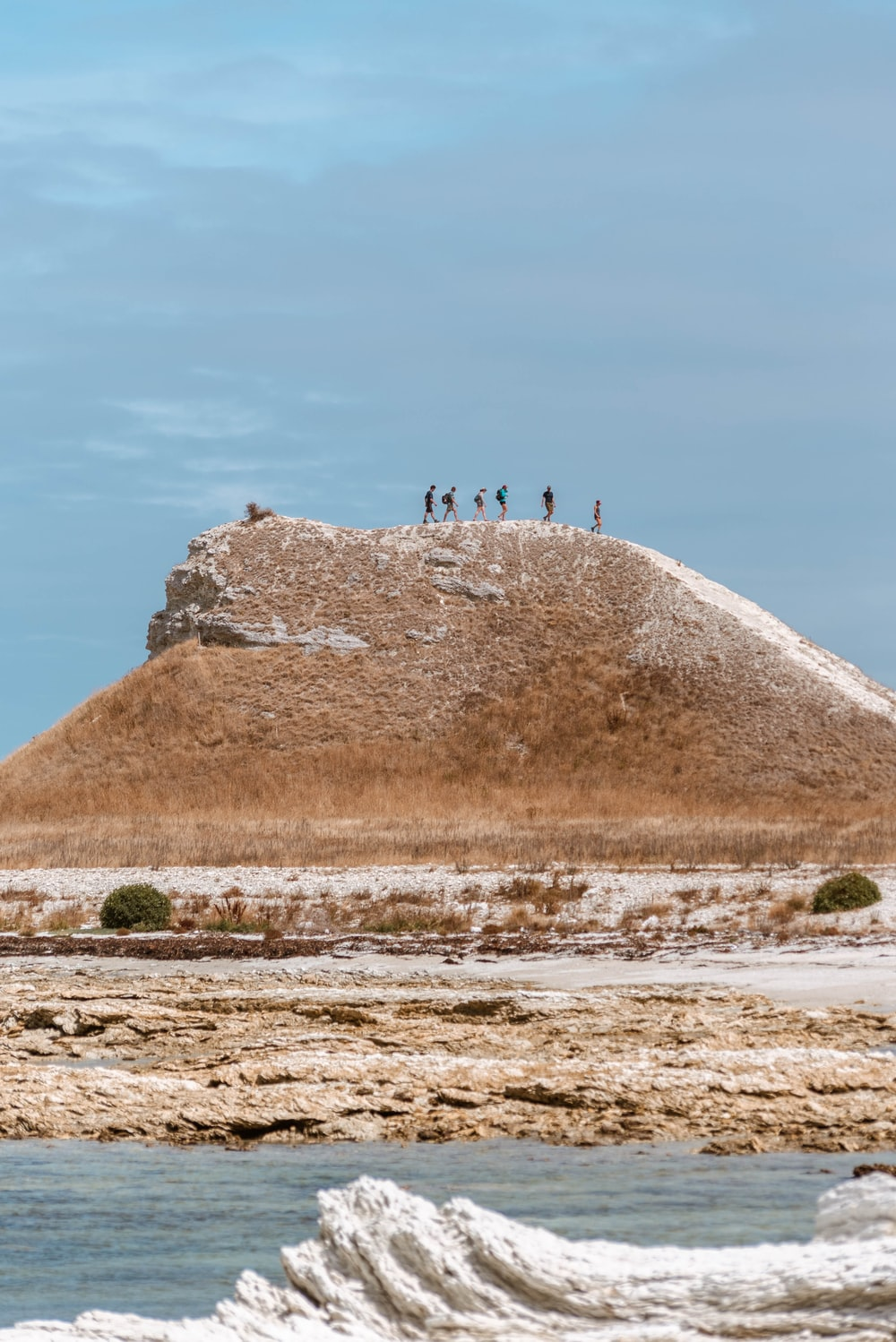people standing on brown rock formation during daytime