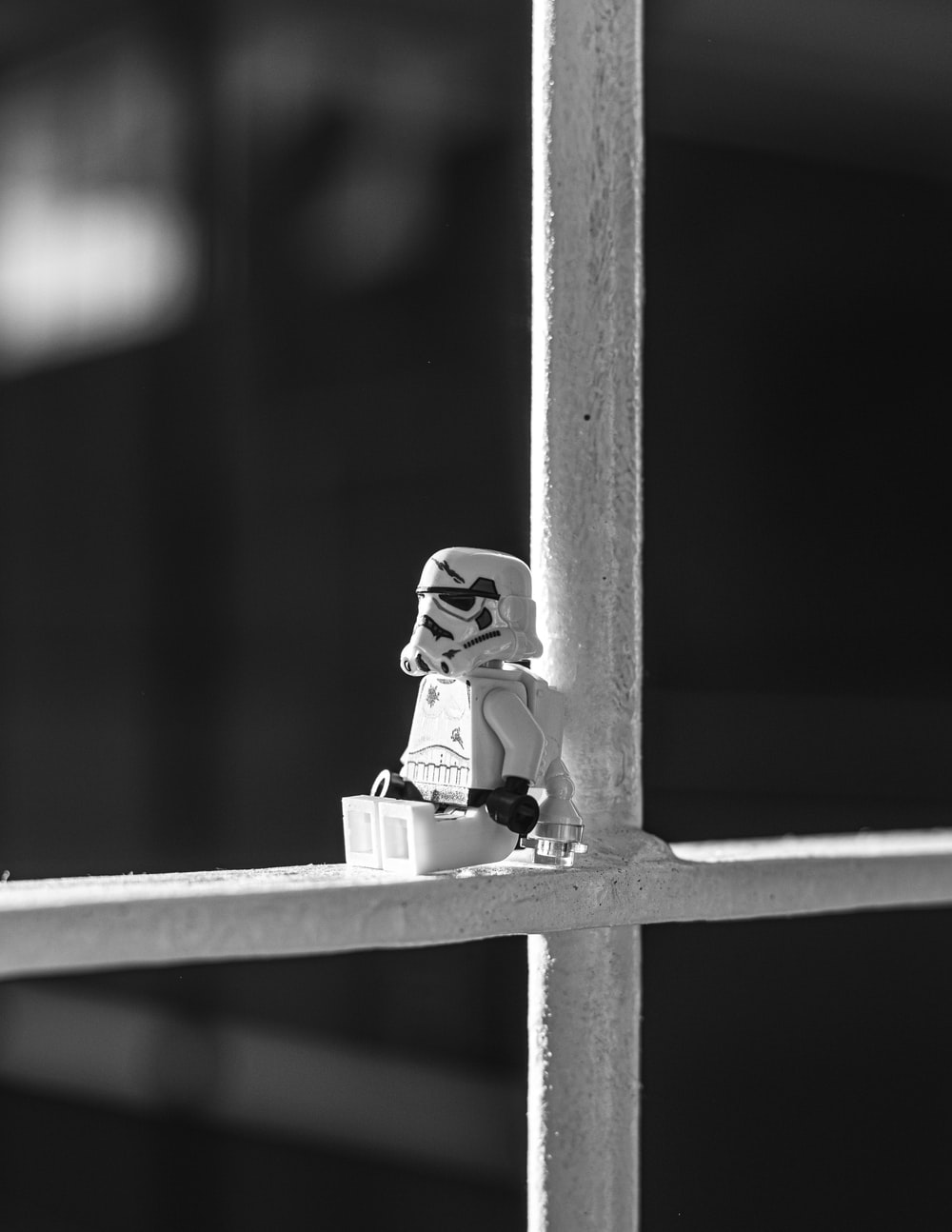 grayscale photo of lego mini figure on wooden fence