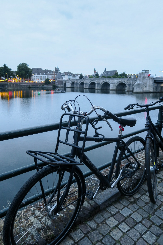 black bicycle parked beside black metal railings near body of water during daytime