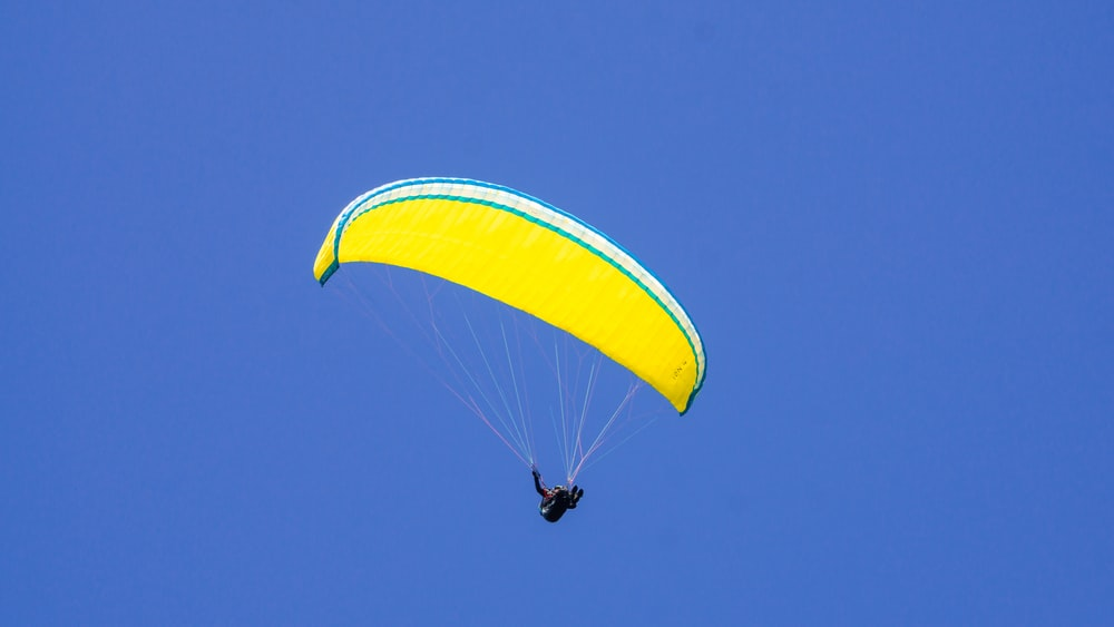person in yellow parachute under blue sky during daytime