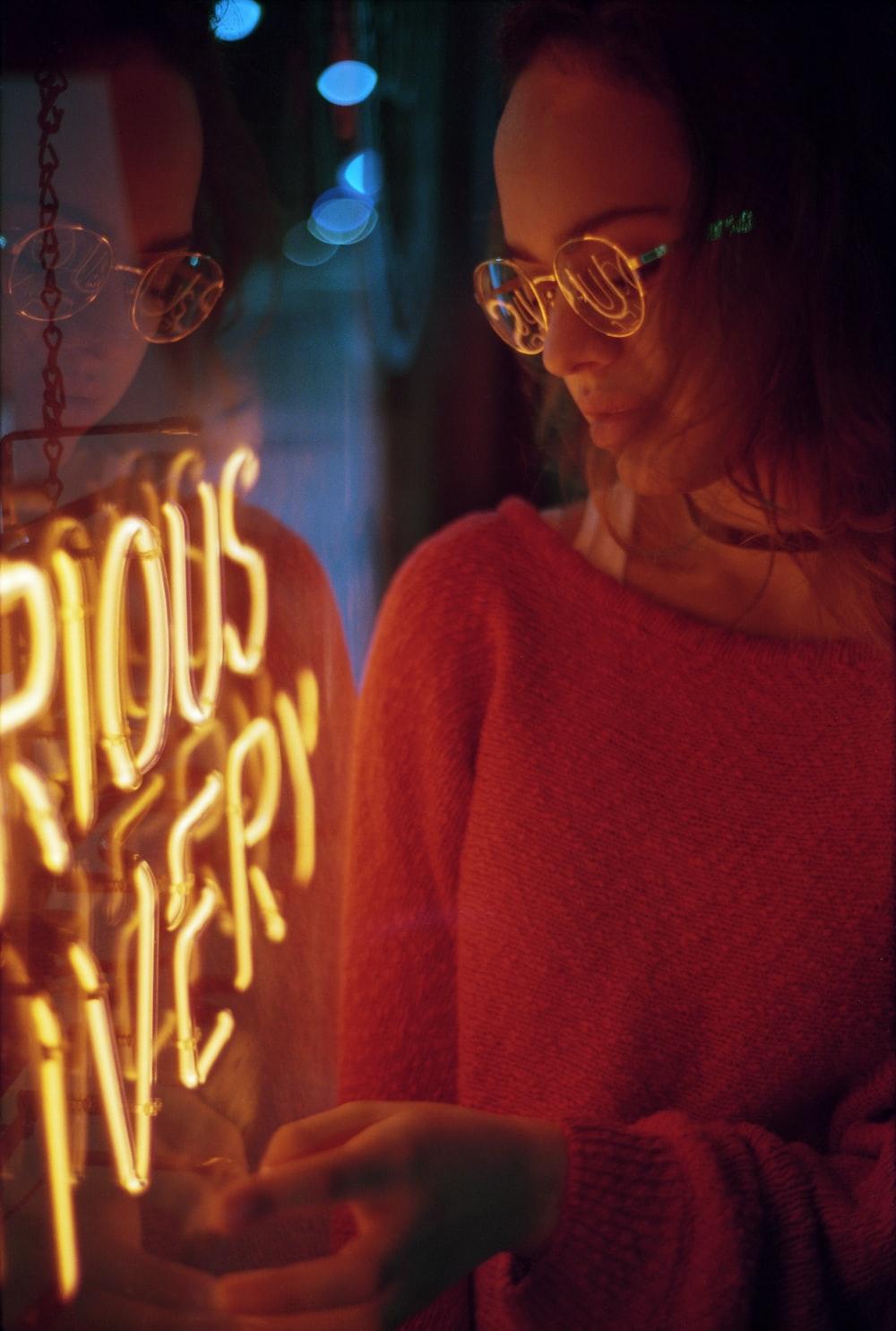 woman in red sweater wearing eyeglasses
