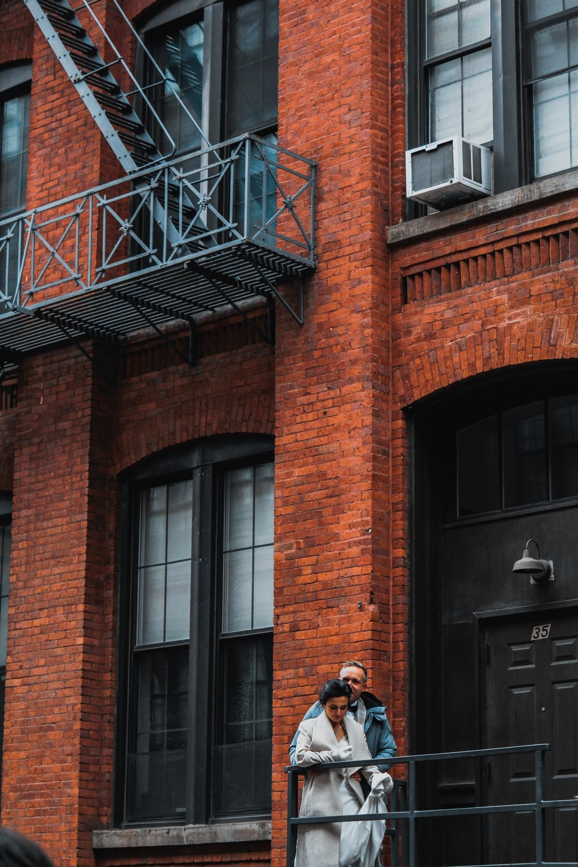 man in black jacket and blue denim jeans standing beside brown brick building during daytime
