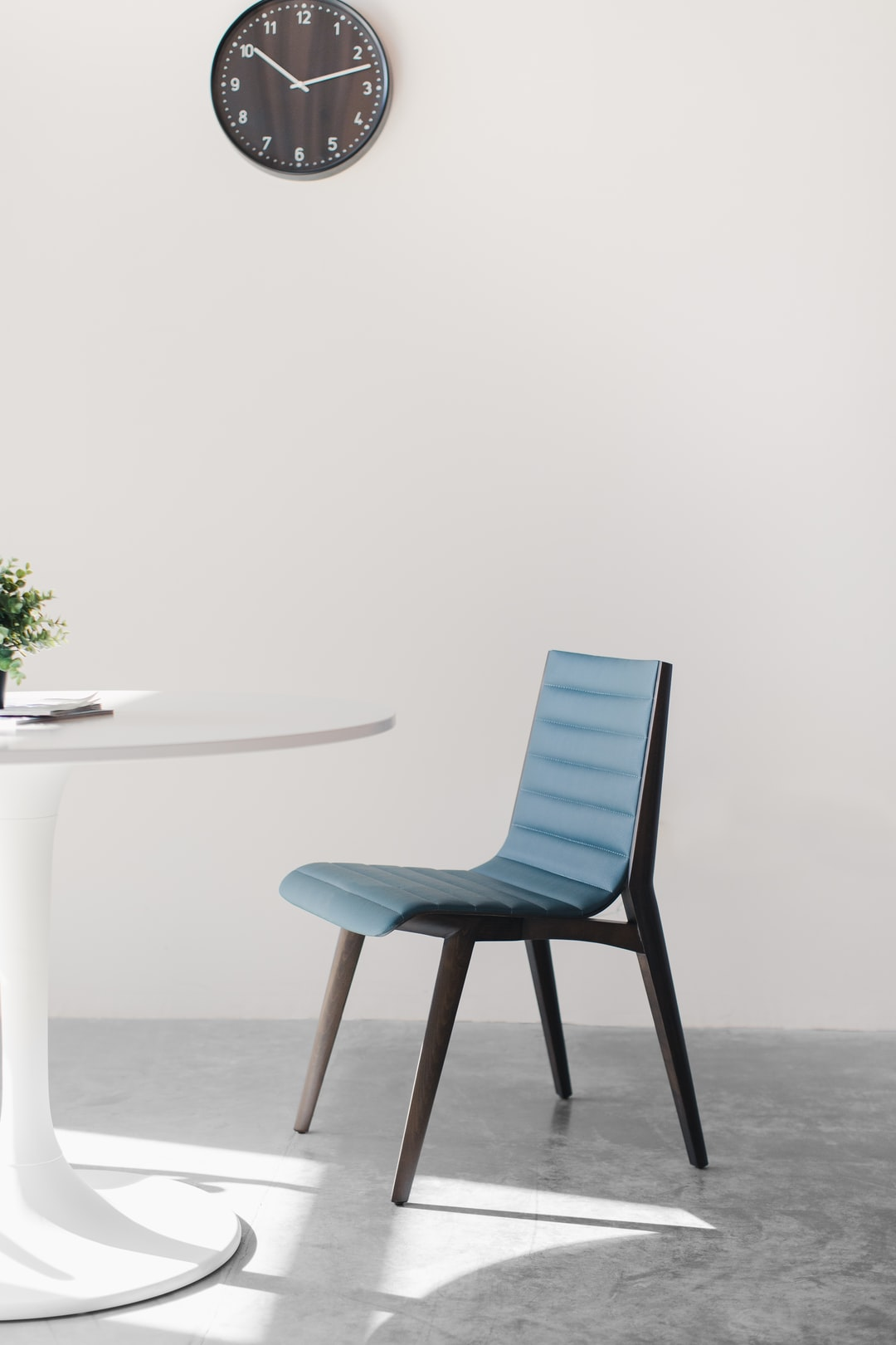 A ribbed mid century modern chair in a brightly lit, minimalist cafe.