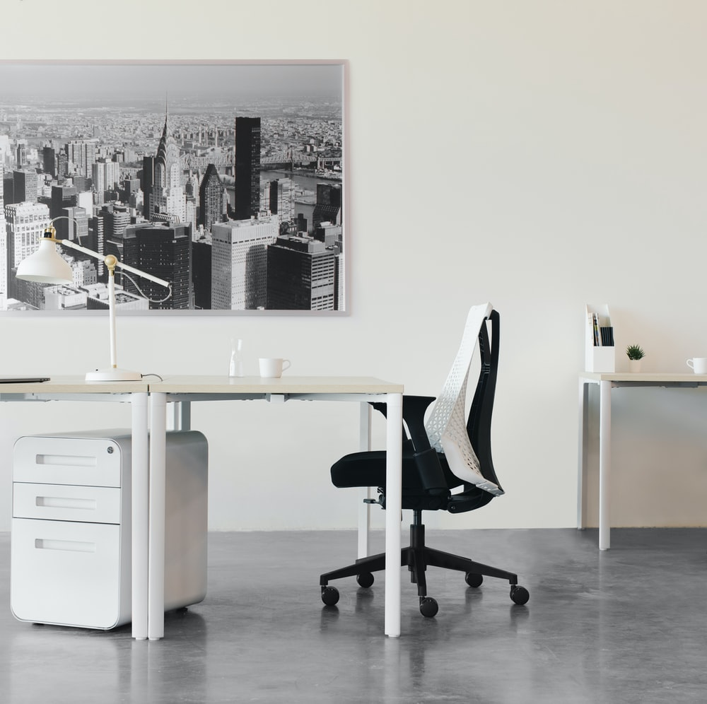 black and white office rolling chair beside white wooden desk