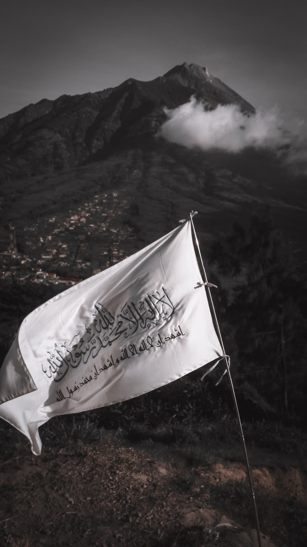 white and blue flag on mountain during daytime