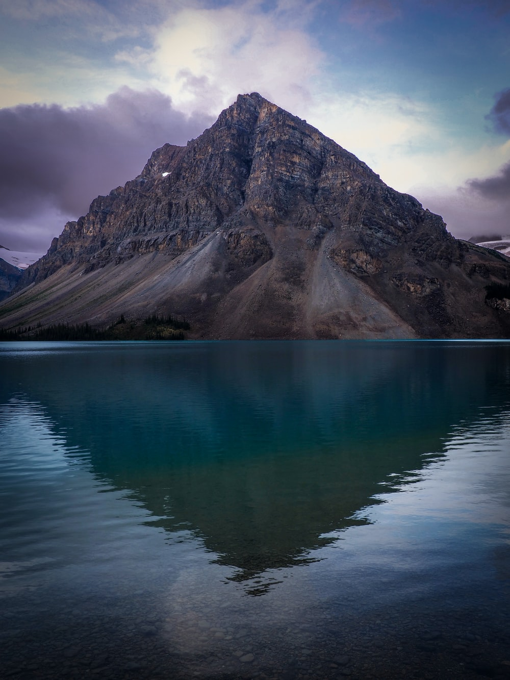 lake near mountain under cloudy sky during daytime