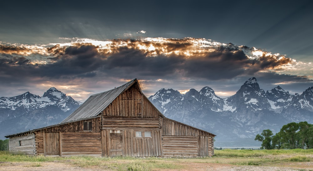 brown wooden barn near snow covered mountain under cloudy sky during daytime