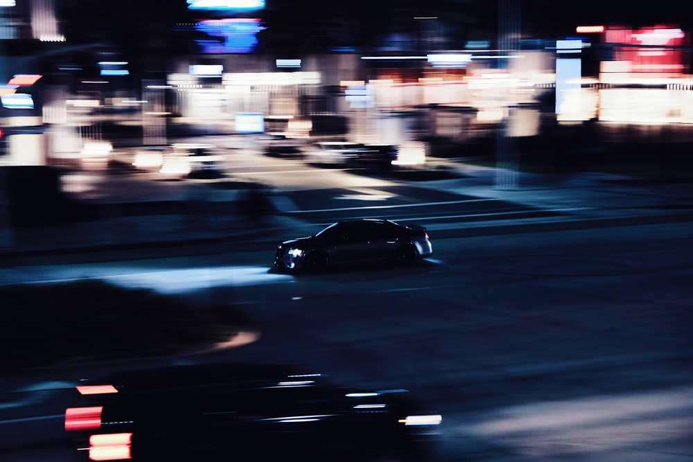 black coupe on road during night time