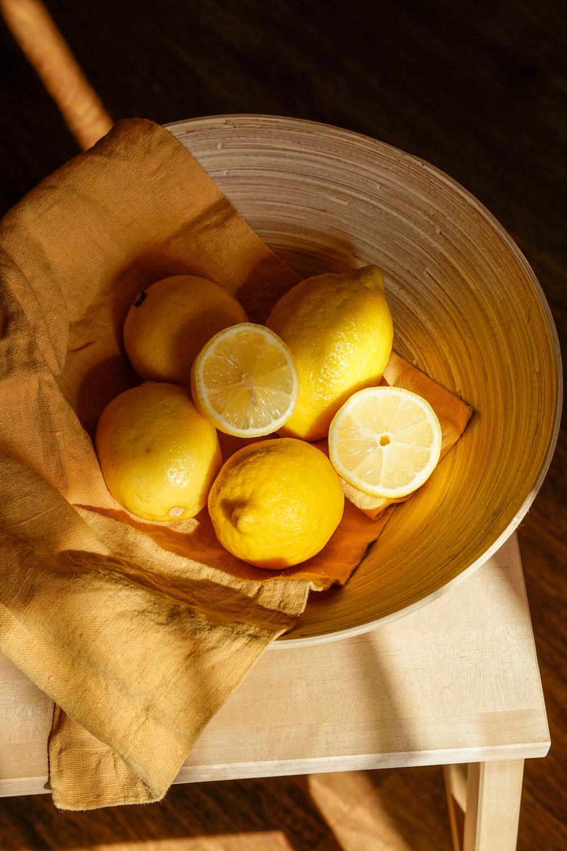 yellow lemon fruit in brown wooden bucket