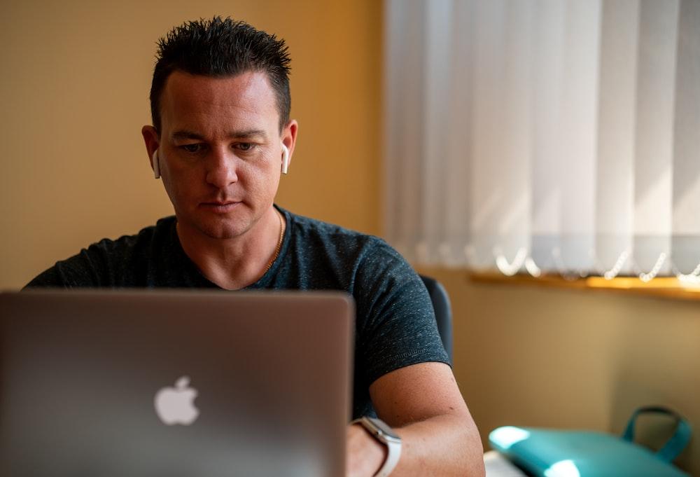 man in blue crew neck t-shirt using silver macbook