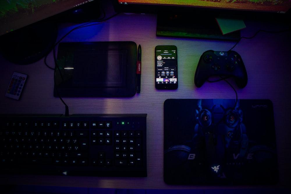 black computer keyboard beside black smartphone