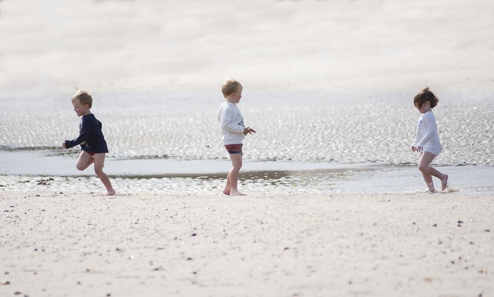 girl in white shirt walking on beach during daytime
