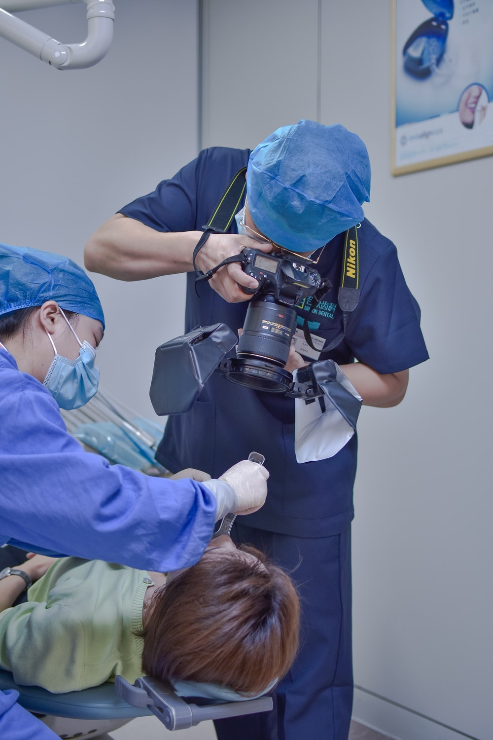 man in blue scrub suit holding black and silver dslr camera