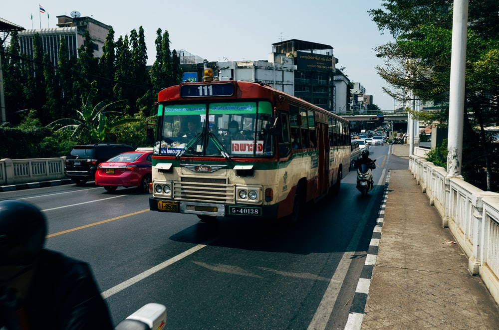 red and white bus on road during daytime